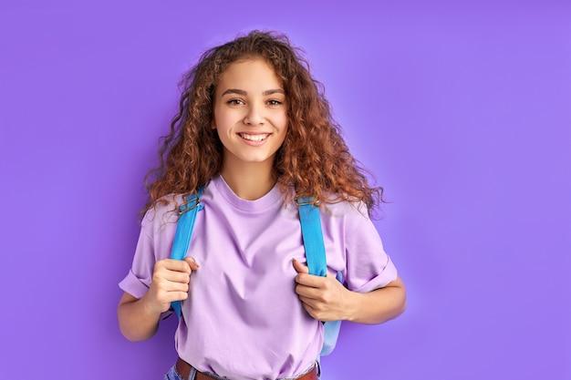 Aluna tímida e diligente, caucasiana, carregando uma bolsa escolar, posando para a câmera, adolescente inteligente isolada no espaço roxo