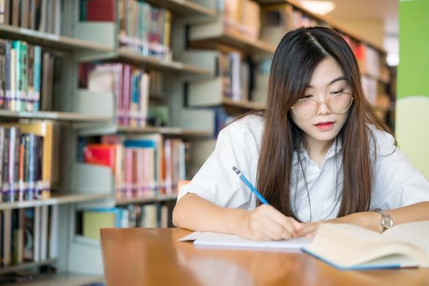 Aluna tomando notas de um livro na biblioteca. jovem, mulher asian, sentando