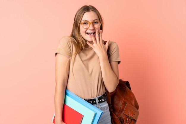 Aluna ucraniana adolescente isolada em rosa com expressão facial de surpresa