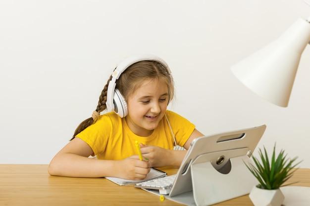 Aluna usa fones de ouvido para estudar online com chamada de vídeo