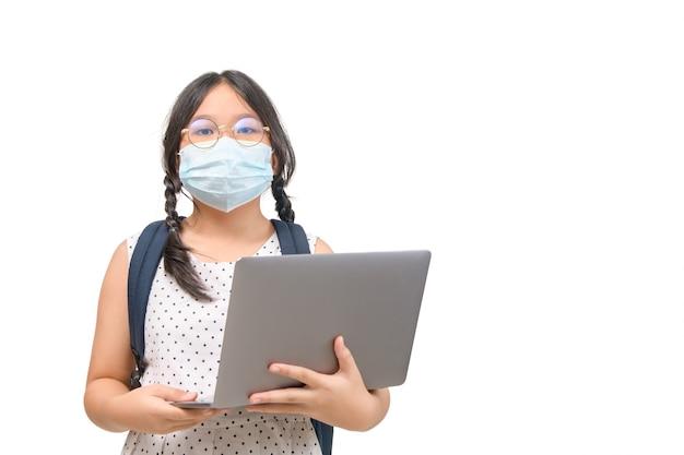 Aluna usa máscara e segura laptop isolado no fundo branco, novo conceito normal e educacional