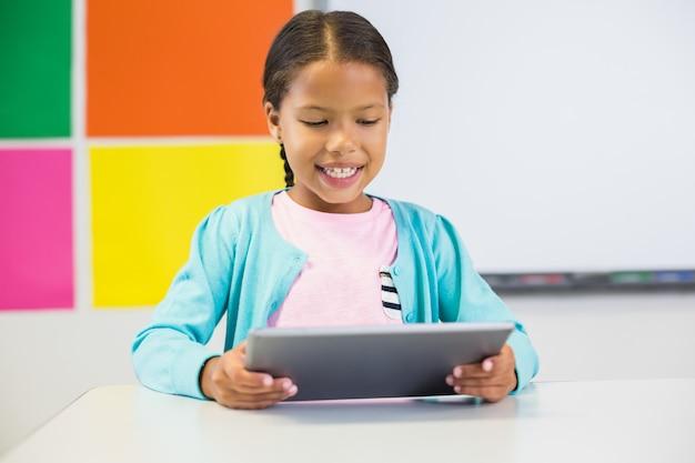 Aluna usando tablet digital em sala de aula