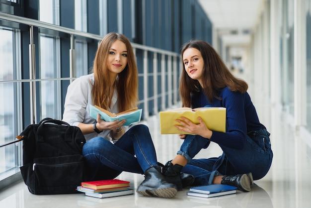 Alunas sentadas no chão lendo notas antes do exame
