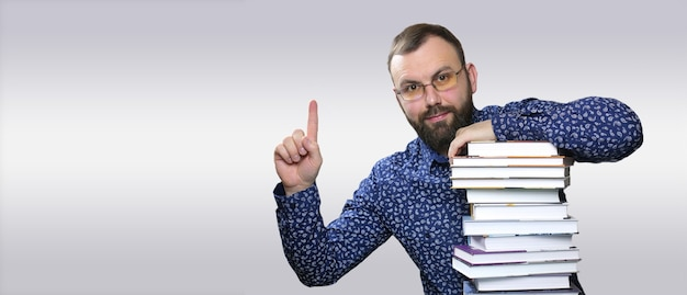 Aluno adulto barba com uma pilha de livros em uma biblioteca