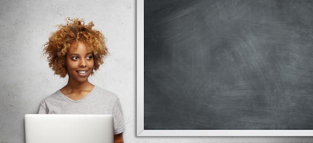 Aluno africano atraente com penteado afro e sorriso fofo, olhando para o lado com expressão pensativa, usando a conexão gratuita à internet no laptop, fazendo trabalhos de aula, sentado no quadro-negro