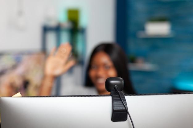 Aluno afro-americano acenando com o professor discutindo aula na universidade durante videochamada online