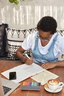 Aluno afro-americano faz exercícios de tradução, reescreve frases no caderno
