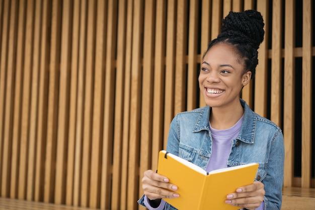 Aluno afro-americano sorridente, estudando e aprendendo algo livro de leitura de preparação para o exame