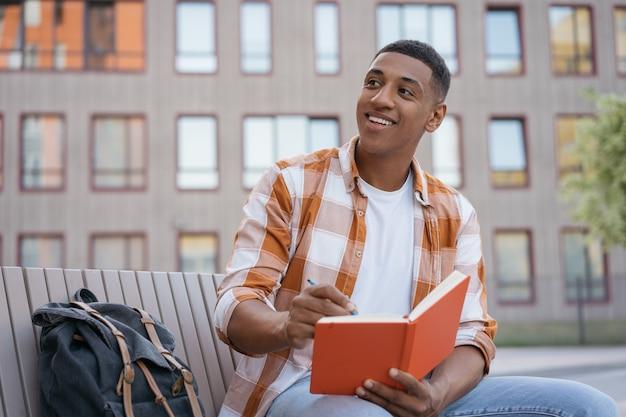 Aluno afro-americano sorridente, estudando e tomando notas de preparação para o exame no campus da universidade