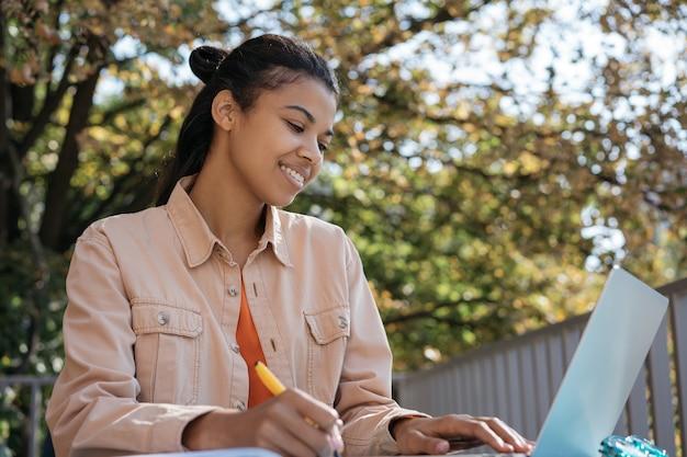 Aluno afro-americano usando laptop, estudando online, aprendendo idiomas