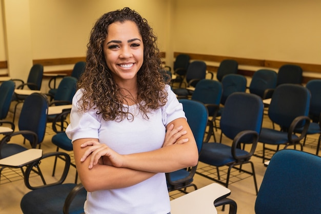 Aluno afro em sala de aula com os braços cruzados, olhando para a câmera sorrindo. jovem estudante com a sala de aula em segundo plano.