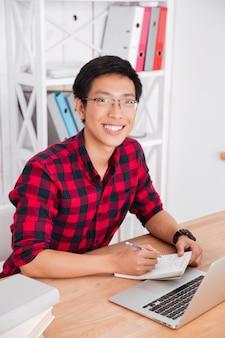 Aluno alegre olhando para frente e trabalhando com ele laptop em sala de aula. sentado perto de livros. escrever notas no caderno