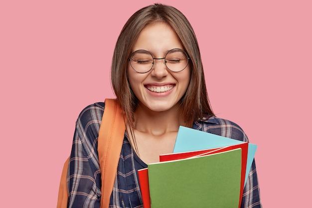 Aluno alegre posando contra a parede rosa com óculos