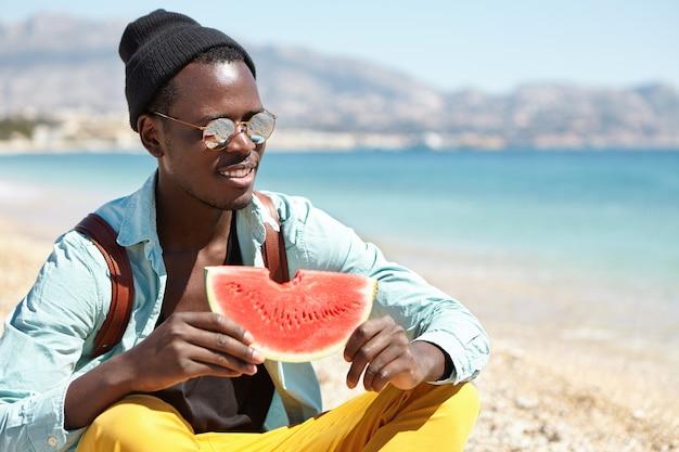 Aluno alegre sentado de pernas cruzadas em uma praia de seixos e comendo melancia com suco fresco