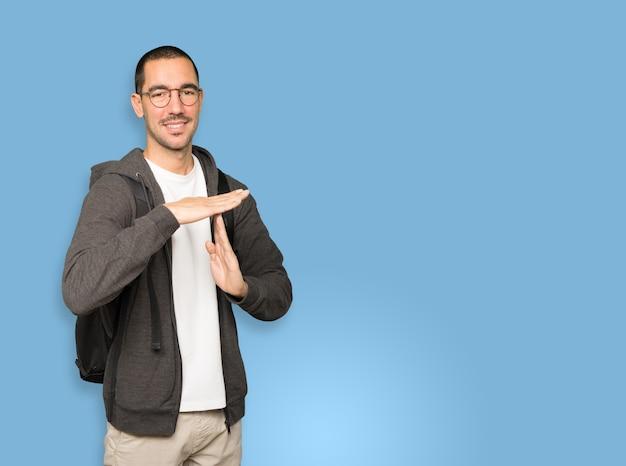 Aluno amigável fazendo um gesto de pausa com as mãos