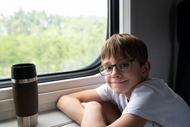 Aluno anda no trem. menino com óculos se senta à mesa do trem. viaje de trem.