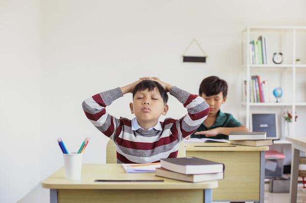 Aluno asiático confuso durante o exame em uma sala de aula