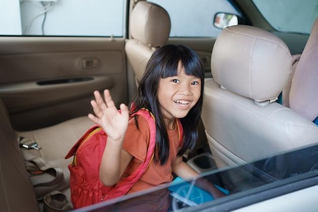 Aluno asiático do ensino fundamental sentado no carro e acenando um tchau enquanto vai para a escola pela manhã