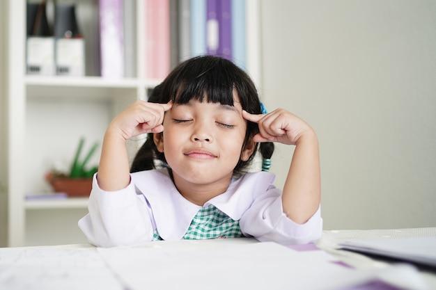 Aluno asiático está pensando na lição de casa na escola