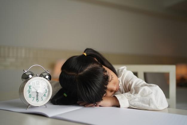 Aluno asiático gril dormindo enquanto lê o livro no quarto durante o período noturno