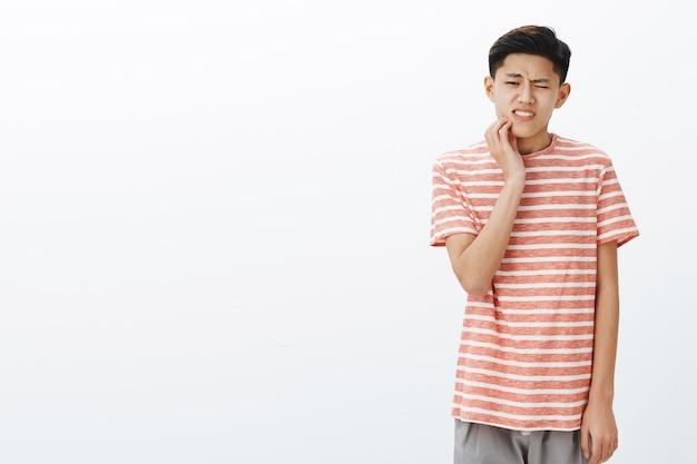 Aluno asiático jovem e atraente inquieto tendo cáries tocando a bochecha, reagindo à dor, com dentes podres