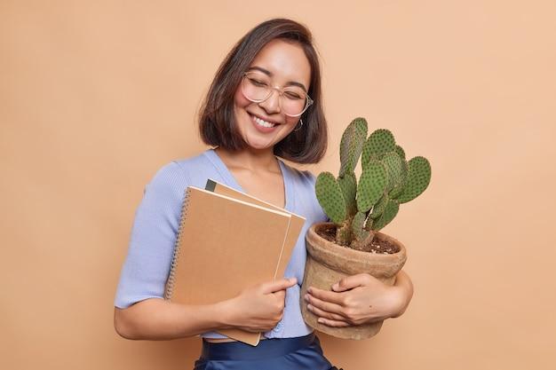 Aluno asiático muito alegre se sente satisfeito depois de passar no exame carregando cadernos e cactos em vasos usando óculos transparentes poses casuais de macacão contra uma parede bege