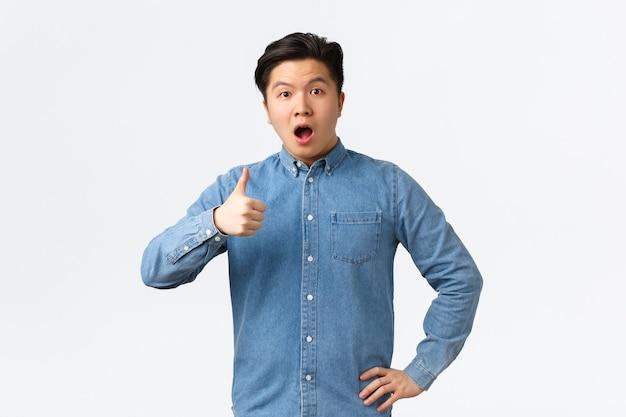 Aluno asiático surpreso e impressionado abriu a boca fascinado, mostrando os polegares para cima espantado, dizendo uau, avalie um bom trabalho, dizendo bem feito ou bom trabalho, fundo branco em pé.
