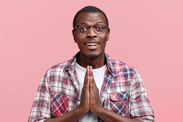 Aluno atraente jovem mantém as mãos em gesto de oração, pede uma boa nota ao professor, vestido com uma camisa xadrez