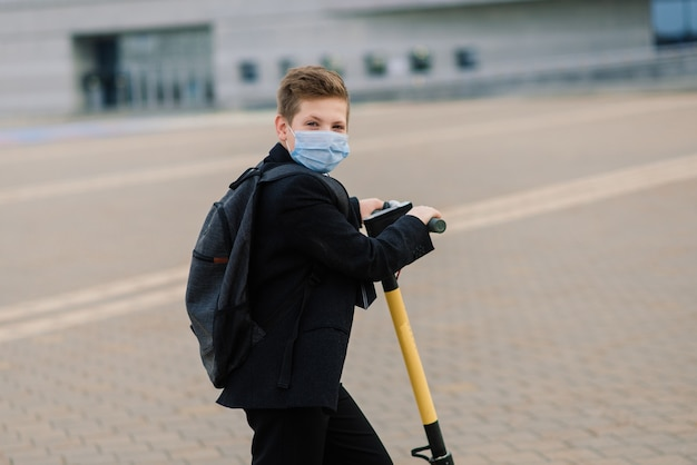 Aluno bonito com máscara protetora dirigindo uma scooter em uma cidade.