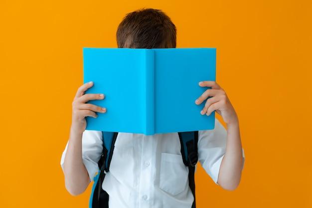 Aluno bonito e inteligente da primeira série escondendo o rosto atrás de um livro didático com fundo amarelo de capa azul