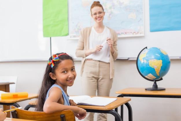 Aluno bonito e professor em sala de aula com globo