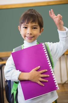 Aluno bonito sorrindo para a câmera em sala de aula, segurando o bloco de notas