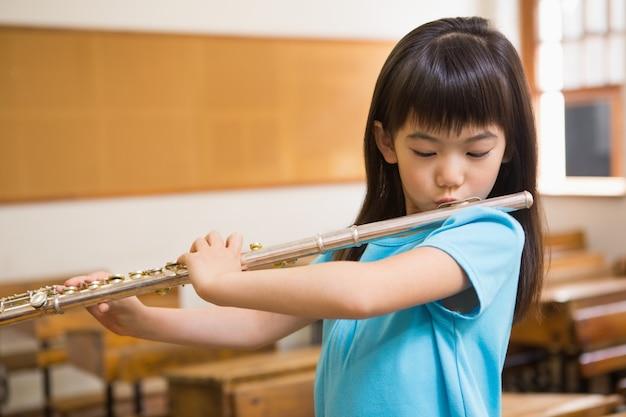 Aluno bonito tocando flauta em sala de aula