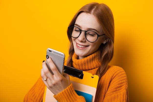 Aluno branco com cabelo ruivo e sardas olhando para o celular e segurando alguns livros