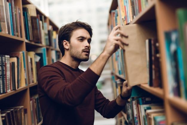 Aluno branco na camisola com livros no corredor da biblioteca.
