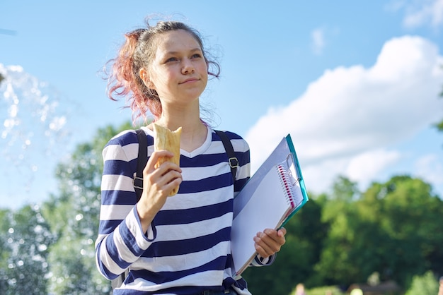 Aluno caminhando ao ar livre com mochila, cadernos e comendo sanduíche
