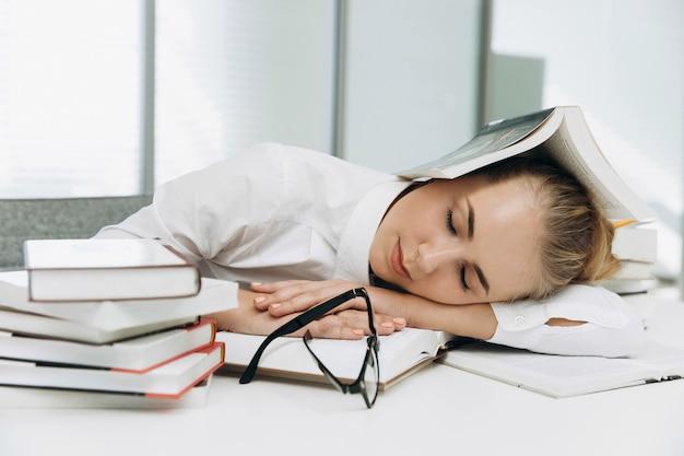 Aluno cansado dorme nos livros na biblioteca