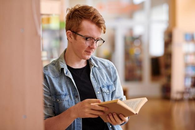 Aluno casual usando óculos, lendo um livro na biblioteca da faculdade enquanto se apoia na estante