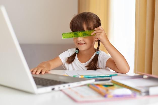 Aluno caucasiano sentado em uma mesa, olhando para o visor do laptop, vestindo camiseta branca, cobrindo os olhos com a régua verde. ensino à distância, educação online, lição de casa, volta às aulas.