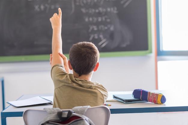 Aluno com as mãos em sala de aula durante uma aula
