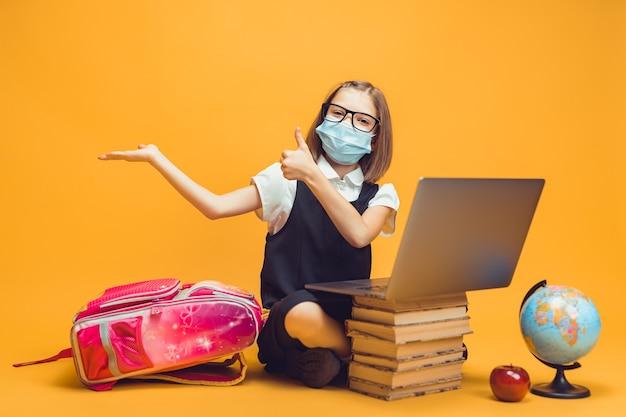 Aluno com máscara médica está sentado atrás de uma pilha de livros e o laptop aponta para o espaço vazio mostra o polegar para cima