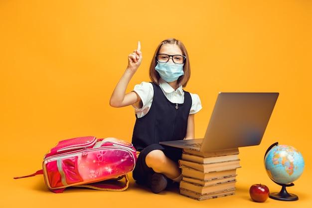 Aluno com máscara médica sentado atrás de uma pilha de livros e um laptop levantando o dedo indicador para a educação infantil