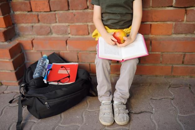 Aluno com mochila grande e lancheira sentou-se para almoçar perto do prédio da escola.