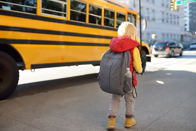 Aluno com mochila perto de ônibus escolar amarelo