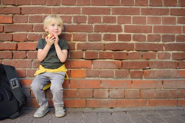 Aluno com mochila sentou-se para comer maçã perto do prédio da escola.