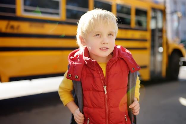 Aluno com o schoolbag com o ônibus escolar amarelo no fundo.