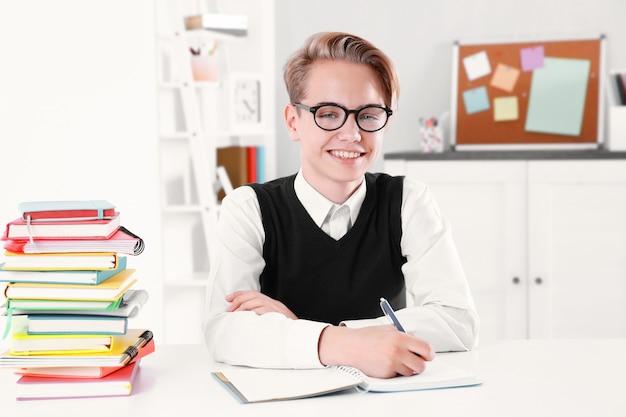 Aluno com pilha de livros sentado na mesa de uma sala de aula