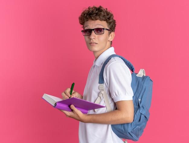 Aluno com roupas casuais, óculos e mochila segurando o livro