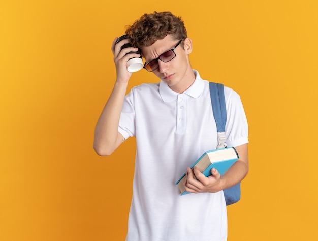 Aluno com roupas casuais usando óculos e mochila segurando um livro e um copo de papel parecendo cansado