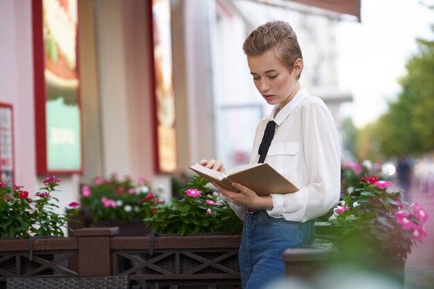 Aluno com um livro nas mãos, ao ar livre, descanse com a diversão caminhando pela cidade.